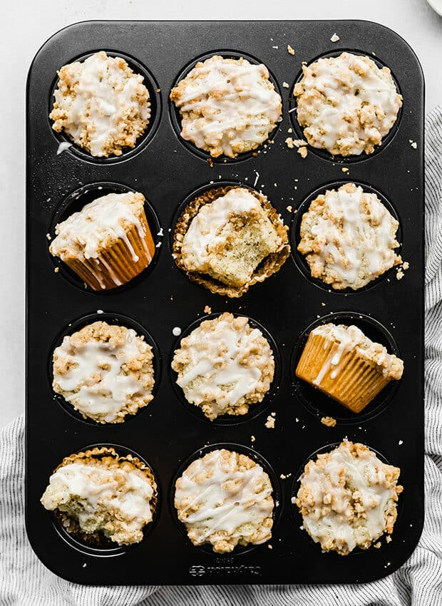 A muffin tin full of baked lemon poppy seed muffins.