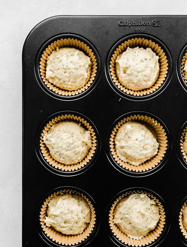 A muffin tin filled with lemon poppy seed muffin batter.