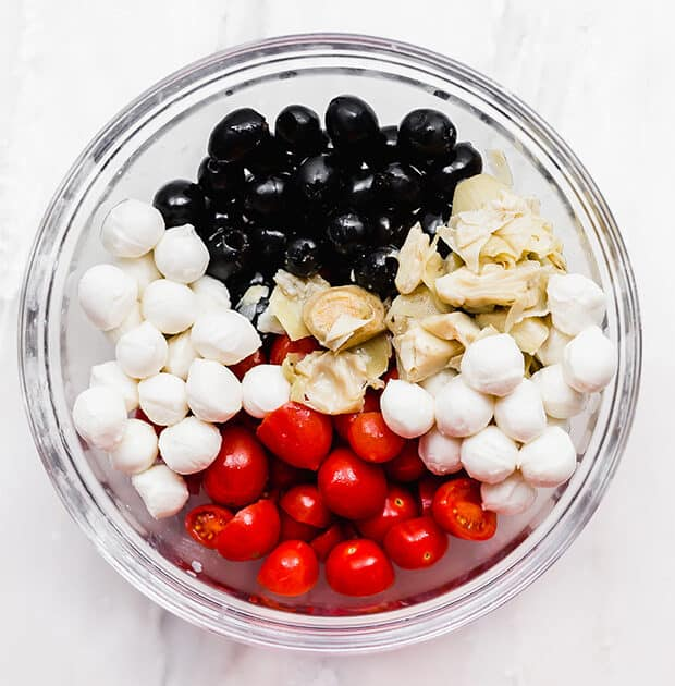 A bowl with mozzarella balls, tomatoes, olives, and artichokes in it.