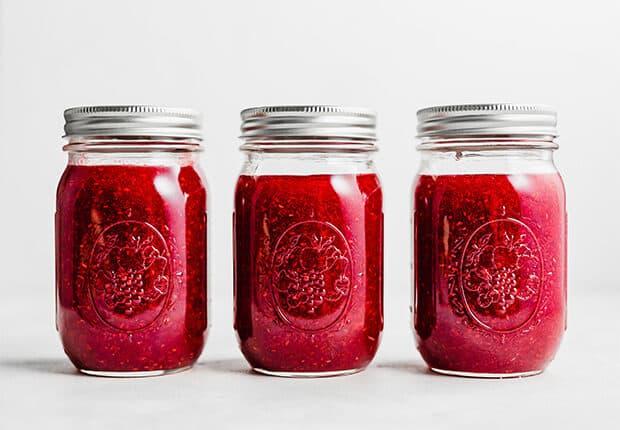 Three glass jars full of homemade raspberry freezer jam.