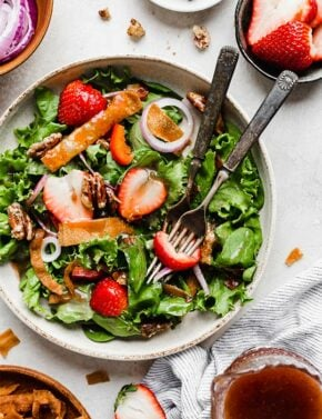 Two forks in a bowl of Strawberry Spinach Salad.