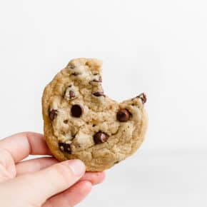 A hand holding a tahini chocolate chip cookie against a white background.