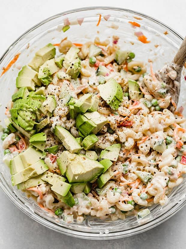 Diced avocados overtop a tuna macaroni salad.