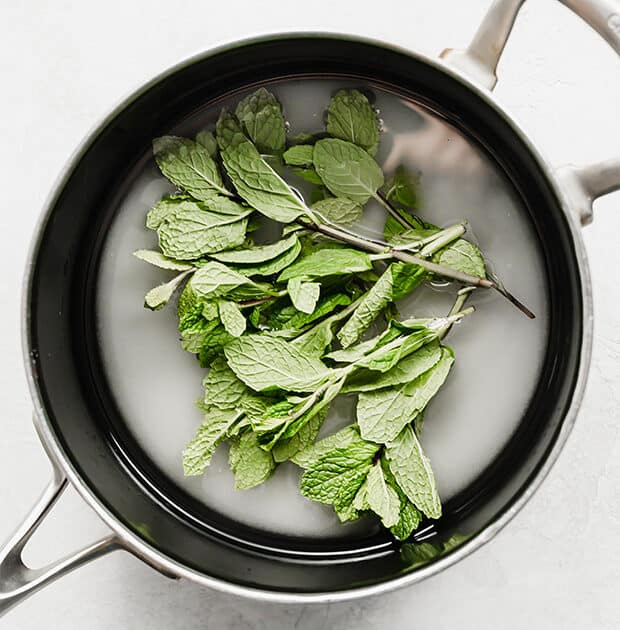 A saucepan with sugar, water, and mint leaves.
