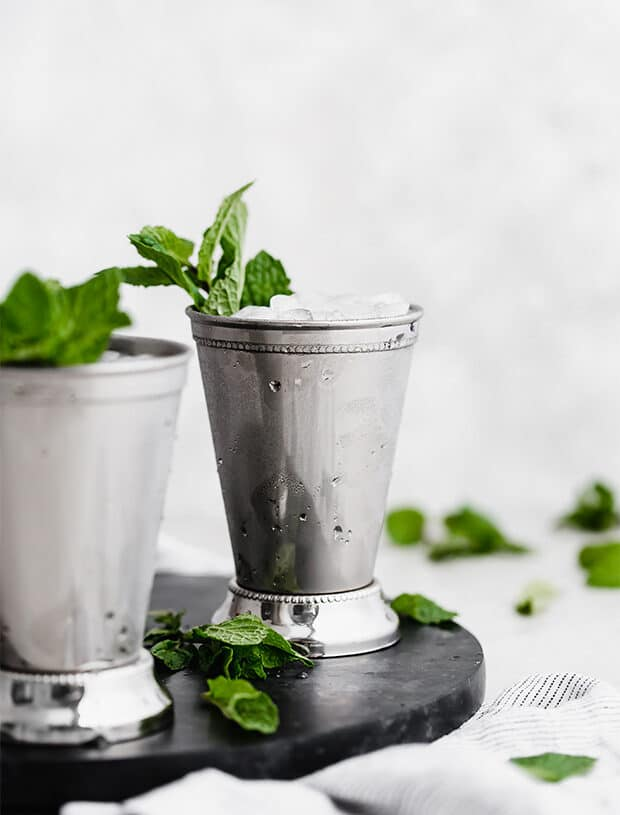 A straight on photo of a mint julep in a silver cup.