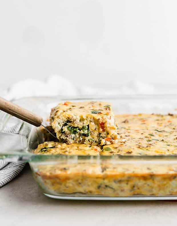 A slice of Breakfast Casserole being lifted out of the pan.