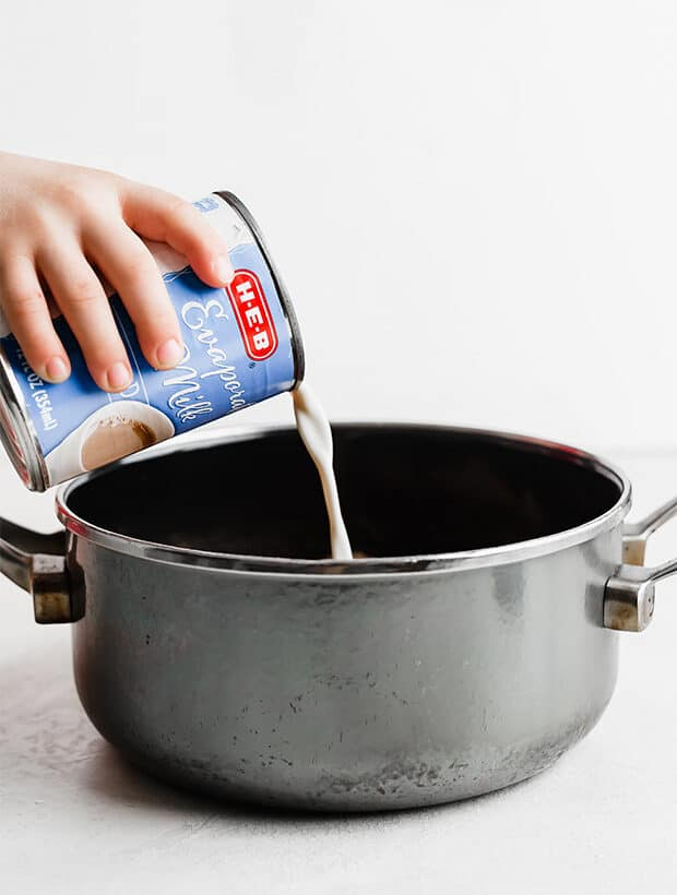A can of evaporated milk being poured into a gray saucepan.