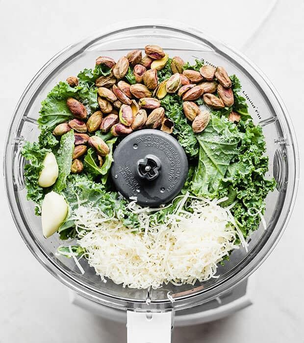 Overhead photo of a food processor full of kale pesto ingredients.