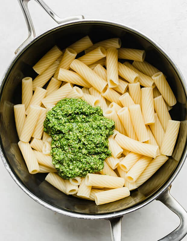 A saucepan with cooked noodles and a dollop of kale pesto over the pasta.