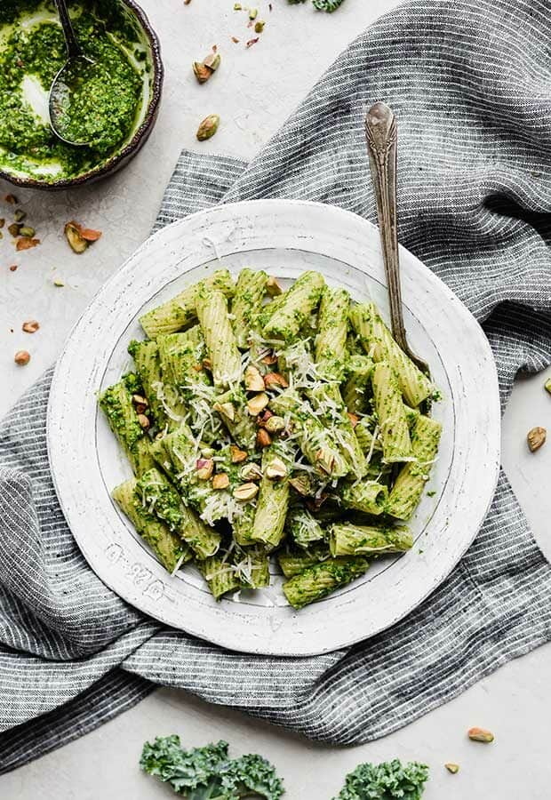 A white plate full of kale pesto pasta, on a gray linen napkin.