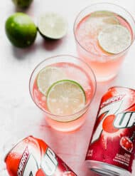 A glass of limeade slush with limes and cherry 7-UP surrounding it.