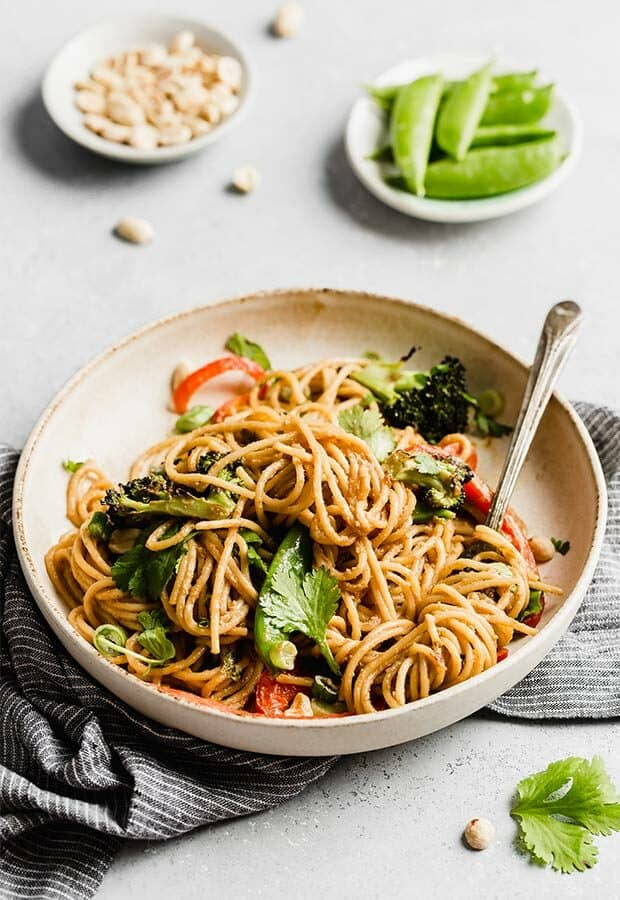 A plate of Peanut Noodles with veggies against a white background.