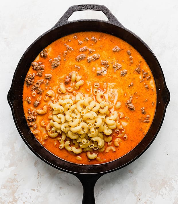 Overhead photo of a cast iron skillet full of a red liquid, ground beef, and large macaroni noodles.