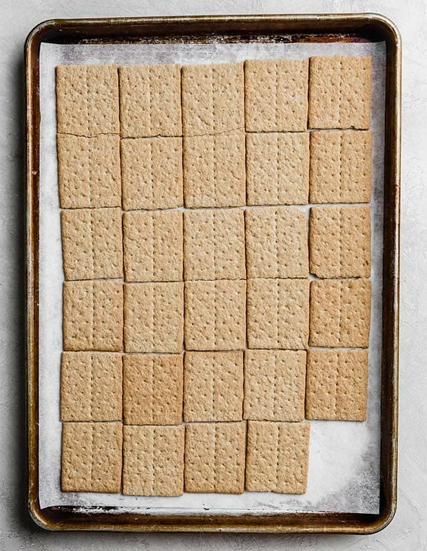 A baking sheet lined with parchment paper and covered with graham cracker squares.