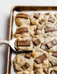 A baking sheet full of back-to-back s'mores cookies, with a spatula lifting a cookie off the sheet.