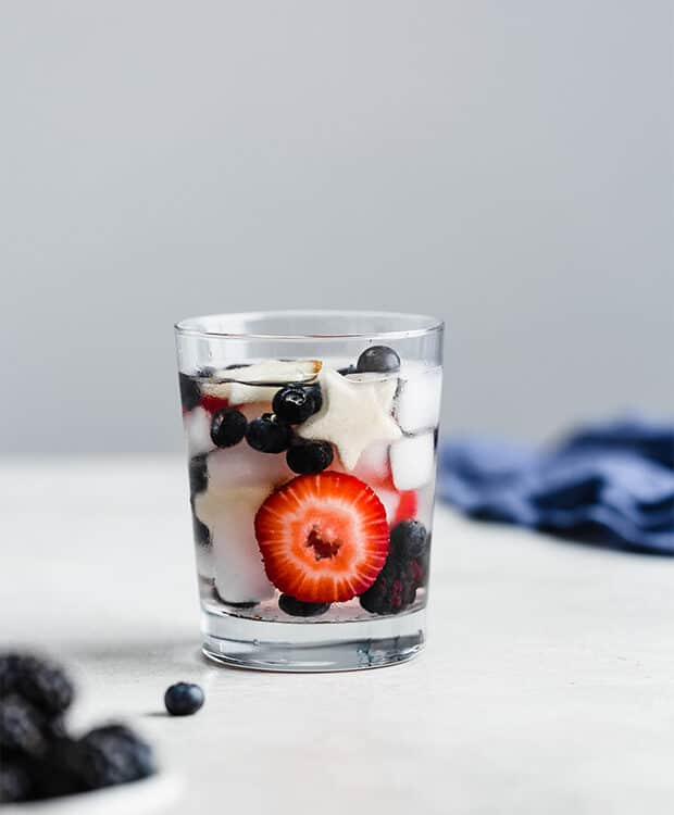 A small glass cup full of water, strawberries, blueberries, and blackberries.