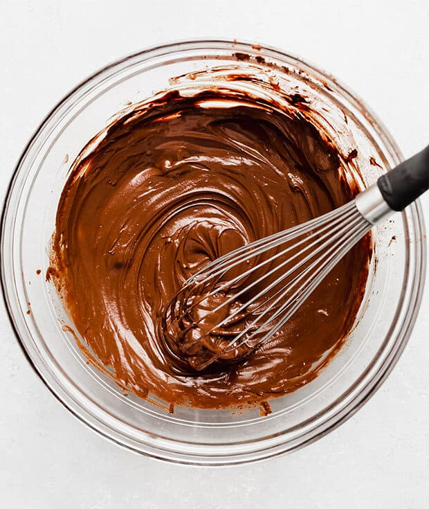 A whisk stirring a smooth chocolate mixture in a glass bowl.
