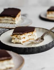 Slice of Chocolate Eclair Cake on a plate, with a fork next to the cake.