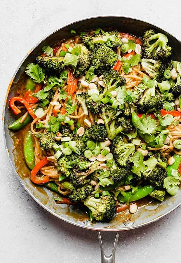 A skillet of peanut noodles with roasted broccoli, sliced red peppers, peas, and peanuts.