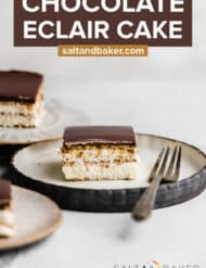 A slice of Eclair Cake topped with chocolate glaze on a plate, with a fork next to the cake.