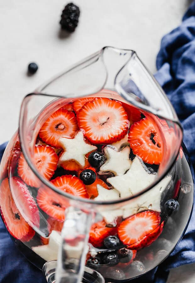 Close up of sliced strawberries, blueberries, and star shaped apples in a glass pitcher.