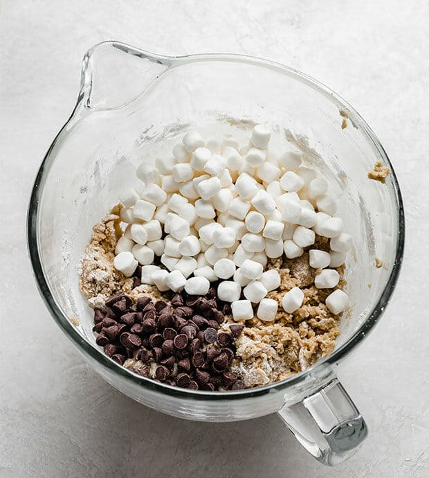 A glass mixing bowl with cookie dough batter, marshmallows, and chocolate chips.