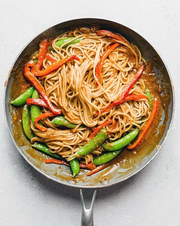 Overhead photo of a skillet full of cooked spaghetti noodles, green peas, and sliced red peppers.