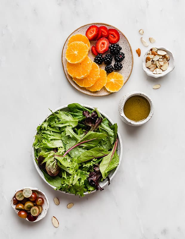 An overhead photo of salad greens, plate of fruit, and bowl full of grapes, and sliced almonds.