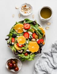 A lettuce salad topped with fresh fruit, sliced almonds, and grapes.
