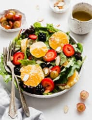 A large plate full of mixed salad greens, topped with sliced oranges, strawberries, grapes, and almonds.