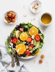 A plate full of salad greens, sliced oranges, almonds, and strawberries.