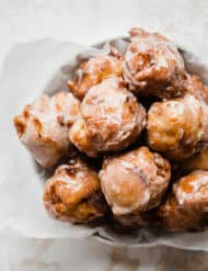 A pile of peach fritters on a plate.