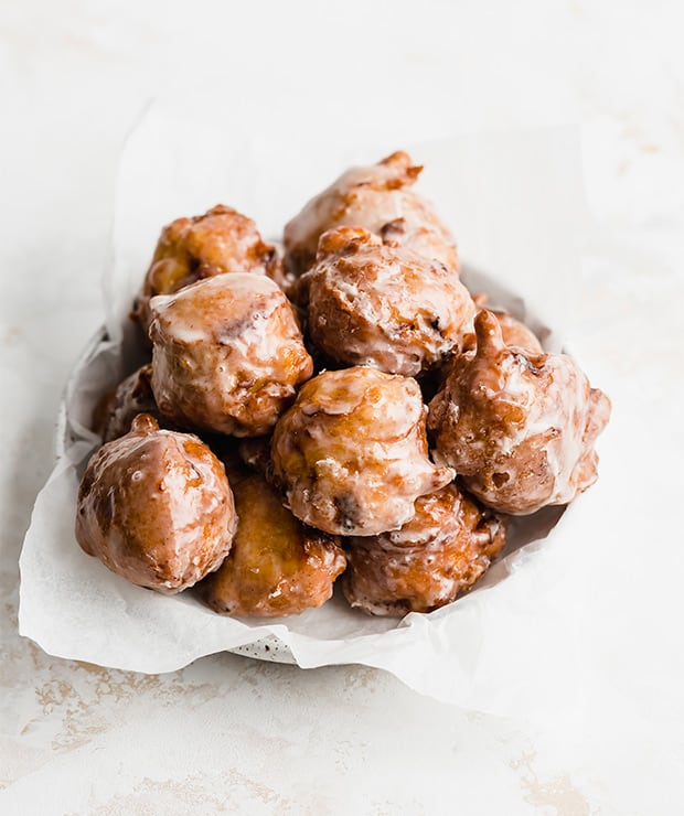 A plate full of homemade peach fritters on a white background.