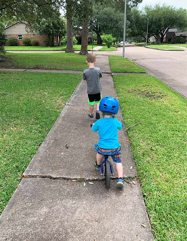 Two boys on a sidewalk.