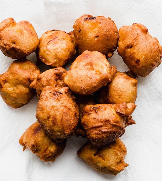 A plate of deep golden brown fried peach fritters.