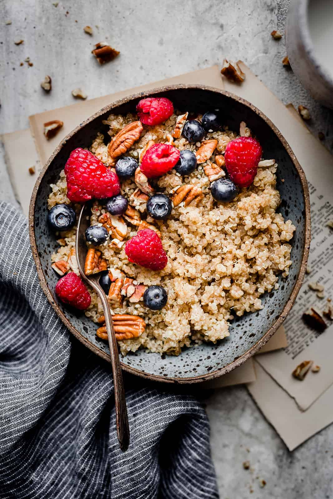 A blue bowl with cooked quinoa that has been topped with fresh fruit.