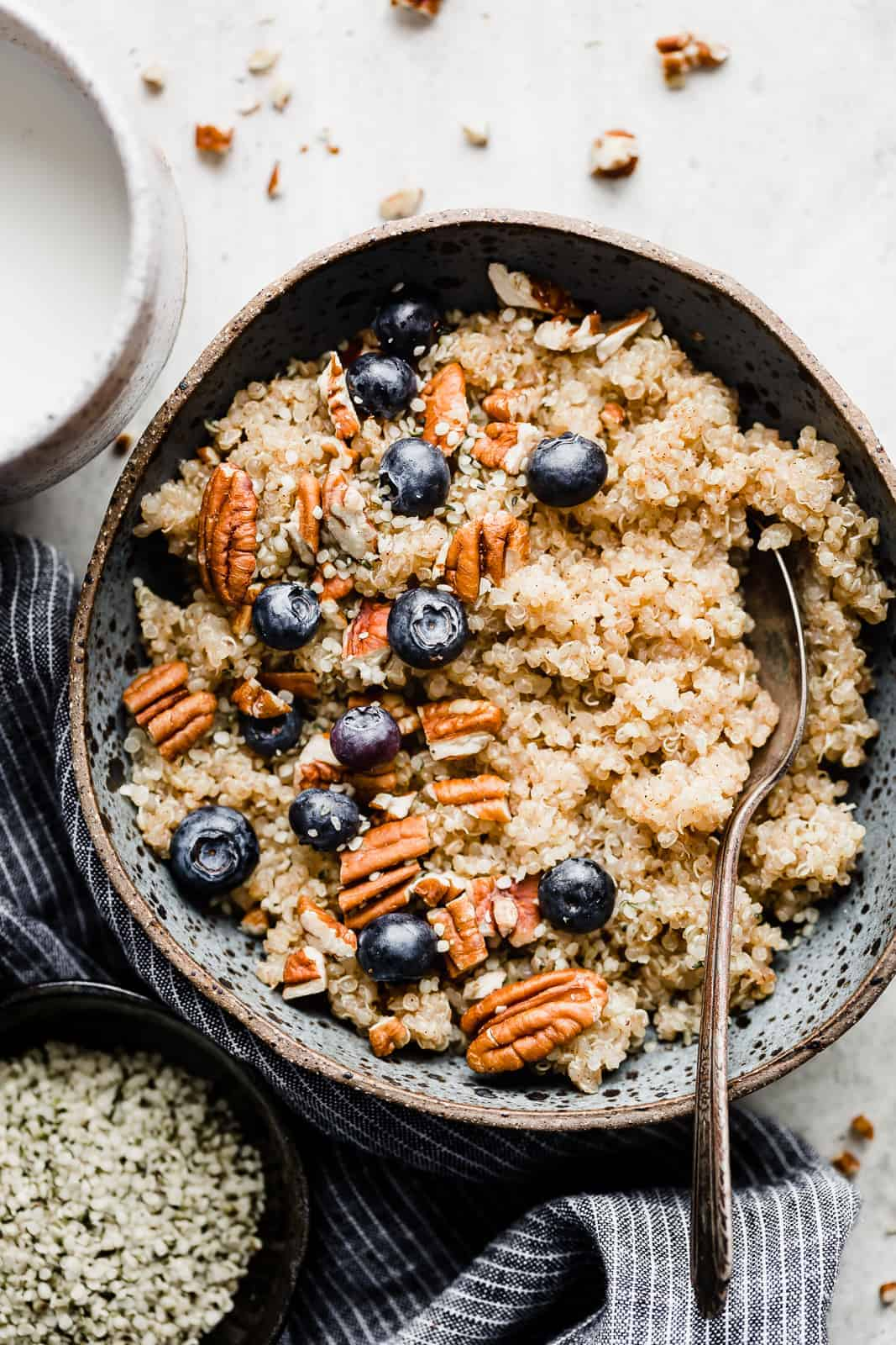 A blue bowl full of breakfast quinoa topped with pecans and blueberries.