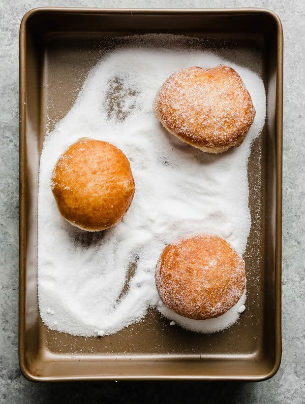 Three fried doughnuts being tossed in granulated sugar.