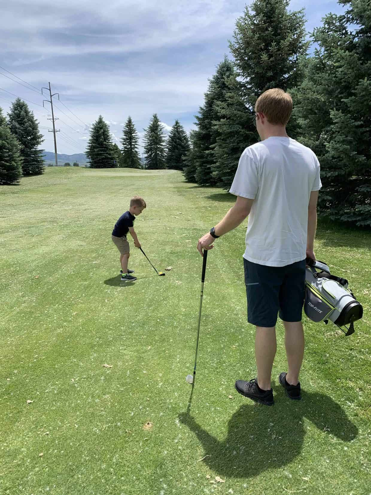A young boy golfing.