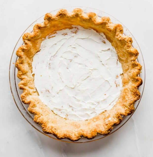 An all-butter pie crust with a smear of cream cheese along the bottom of the crust.
