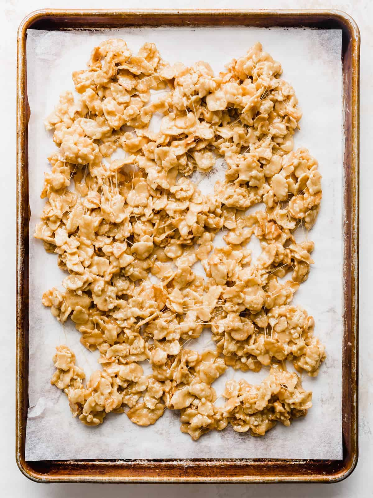 Marshmallowy covered Special K Cereal spread out on a baking sheet.