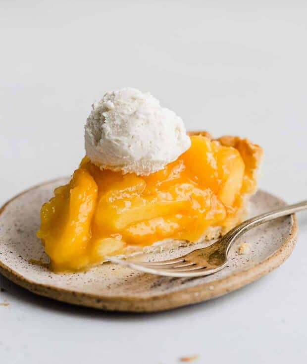 A scoop of vanilla ice cream on a slice of fresh peach pie.