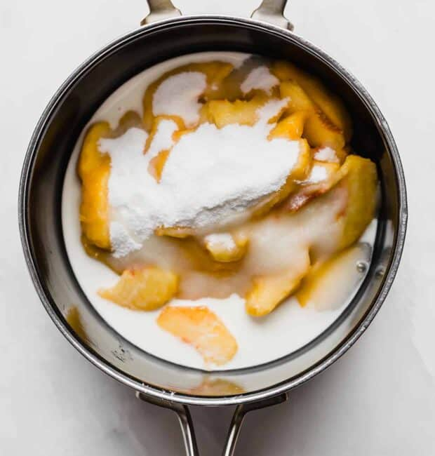 A saucepan with sliced peaches, sugar, and a cornstarch slurry.