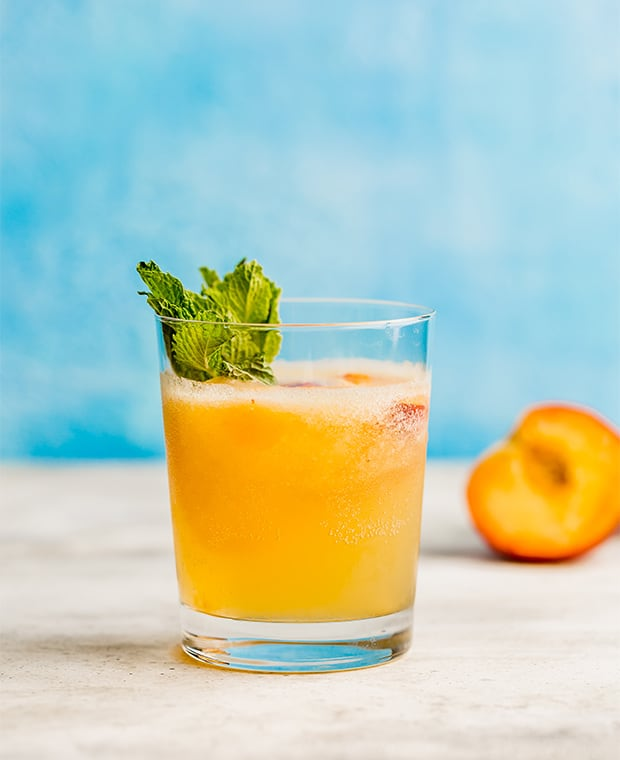 A glass full of peach punch in front of a blue background.