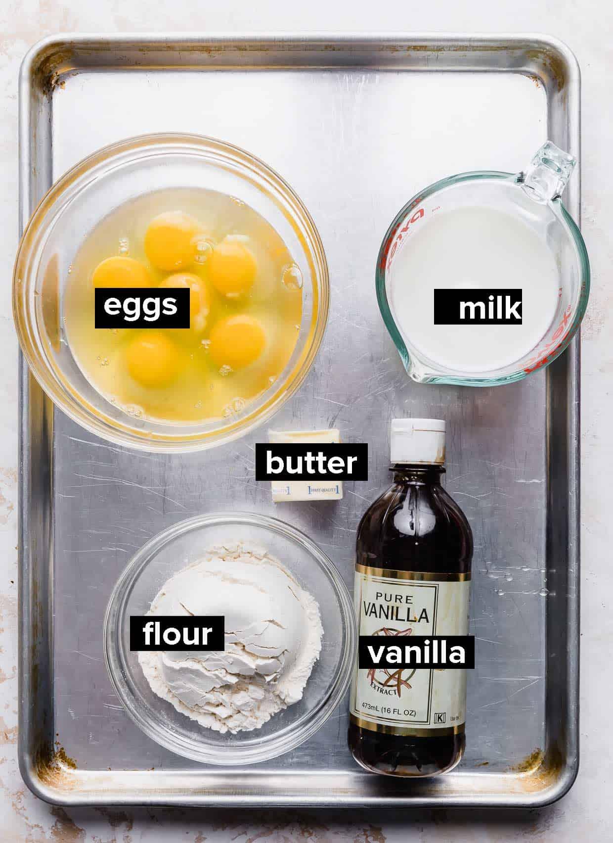Ingredients used to make German pancakes on a baking sheet.