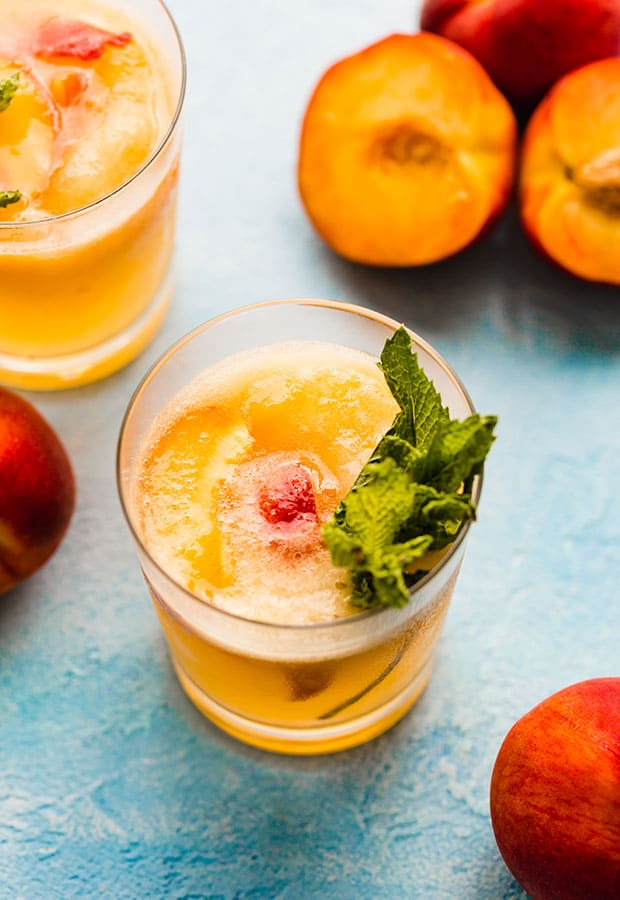 A glass of orange peach punch with slices of fresh peaches in the glass.