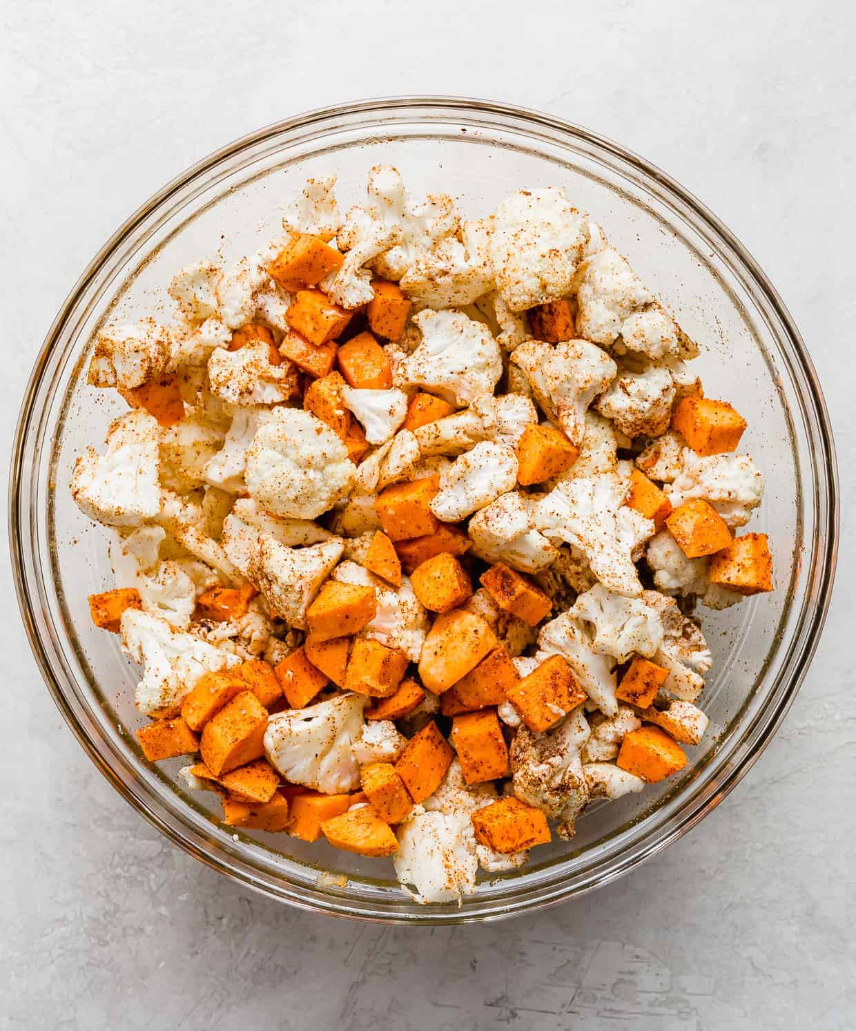 A glass bowl with chopped cauliflower and sweet potatoes in it.