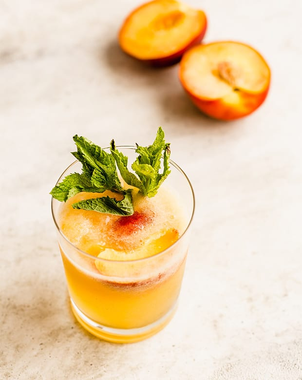Orange colored peach punch in a glass with a sliced peach in the background.