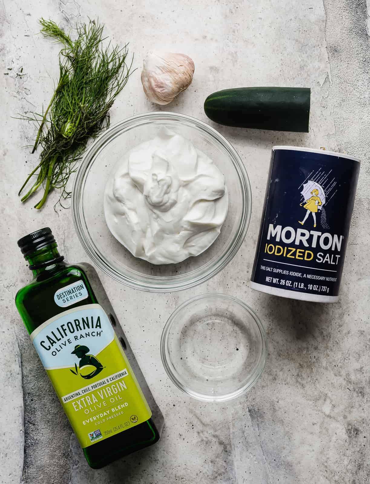 Tzatziki sauce ingredients: olive oil, dill, garlic, yogurt, salt, and cucumber on a grey background.