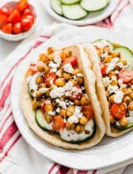 Two Chickpea Gyros on a white plate topped with cucumber, tomatoes, and feta cheese.